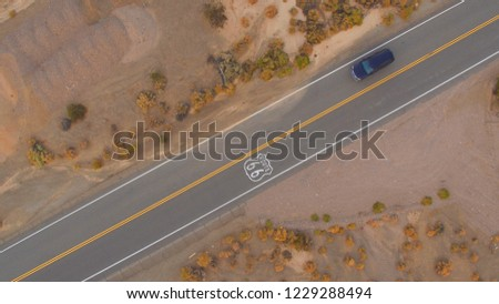 AERIAL: Cars driving along historic Route 66 through the vast desert. People traveling, road trip on empty countryside road through America on sunny summer vacation