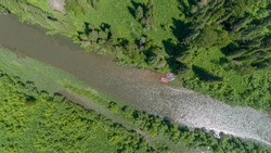 AERIAL: catamaran rafting on a beautiful mountain river in summer. a hike with overcoming obstacles in a high-altitude forest on rafting