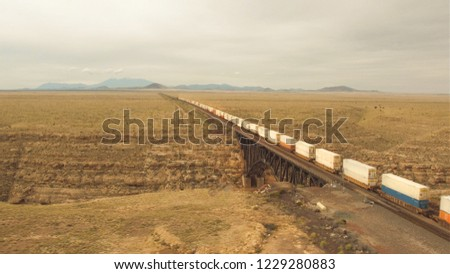 AERIAL: Container freight train crossing steel arch railroad bridge across the Canyon Diablo in the middle of the vast desert in Arizona. Rail freight transport delivering goods