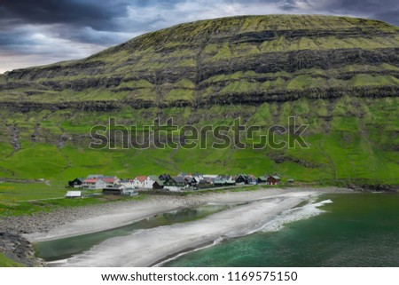 Stock Photo AERIAL: Dark clouds gather over the serene oceanfront village in the picturesque green valley. Stunning background of a tranquil town protected by steep hill in the scenic countryside of Faroe Islands