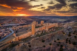 Aerial dramatic sunset view Moline de Aragon large Gothic castle ruin in central Spain with towers and walls built on Moorish origins