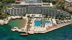 Aerial drone bird's eye photo of famous 5 star luxury 4 seasons hotel and resort in iconic peninsula Vouliagmeni in south Athens riviera , Attica, Greece