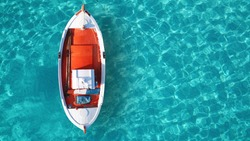 Aerial drone bird's eye top view of colourful traditional fishing boat in turquoise clear sea, Ionian islands, Greece