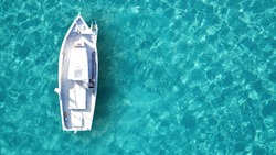 Aerial drone bird's eye top view of white traditional fishing boat in turquoise clear waters, Cyclades, Greece