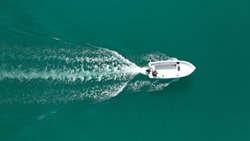Aerial drone bird's eye top view photo of small motor boat cruising in emerald clear water lake
