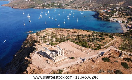 Aerial drone bird's eye view of archaeological site of Cape Sounio and magnificent deep blue bay with yachts docked, Ancient temple of Poseidon, Attica, Greece