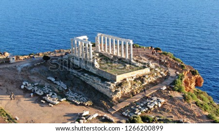 Aerial drone bird's eye view of archaeological site of Cape Sounio and magnificent deep blue bay with iconic Ancient temple of Poseidon, Attica, Greece