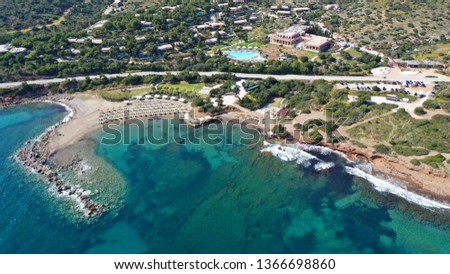 Aerial drone bird's eye view of resort near archaeological site of Cape Sounio with clear turquoise water beach, Attica, Greece