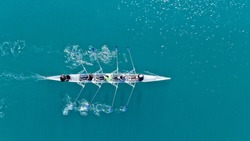 Aerial drone bird's eye view of sport canoe operated by team of young women in deep blue sea waters