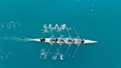Aerial drone bird's eye view of sport canoe operated by team of young women in turquoise clear waters