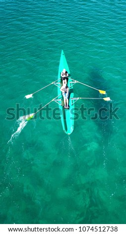 Aerial drone bird's eye view of sport canoe operated by 2 young women in turquoise clear waters #1074512738