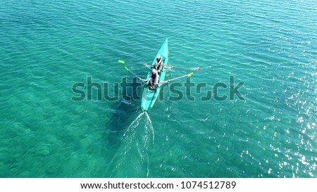 Aerial drone bird's eye view of sport canoe operated by 2 young women in turquoise clear waters #1074512789