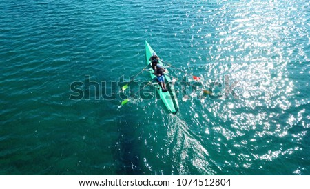 Aerial drone bird's eye view of sport canoe operated by 2 young women in turquoise clear waters #1074512804