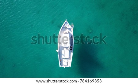 Aerial drone bird's eye view of traditional fishing boat in port of Mykonos in sapphire clear waters, Cyclades, Greece