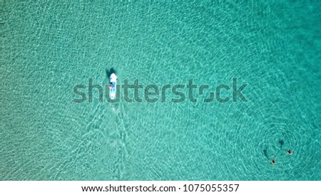Aerial drone bird's eye view of young man exercising sup board in turquoise tropical clear waters #1075055357