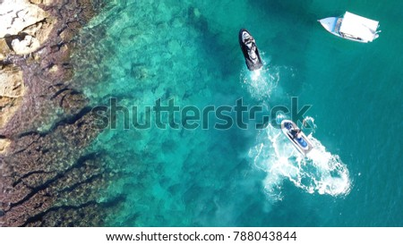 Aerial drone bird's eye view photo of docked jet ski in caribbean turquoise clear waters