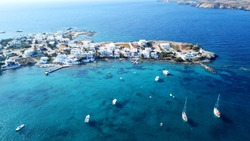 Aerial drone bird's eye view photo of picturesque fishing village of Polonia with traditional fishing boats docked next to island of Kimolos, Milos island, Cyclades, Greece