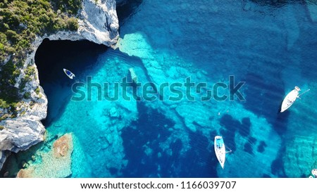 Aerial drone bird's eye view photo of sail boats docked in tropical Caribbean island paradise bay with white rock caves and turquoise clear sea