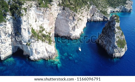 Aerial drone bird's eye view photo of tropical rocky bay of Ortholithos with famous cave of Papanikolis and turquoise calm waters forming a blue lagoon