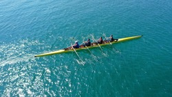 Aerial drone bird's eye view photo of yellow sport canoe operated by team of young team in emerald clear sea