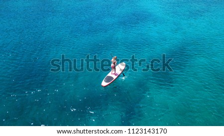 Aerial drone bird's eye view photo of young woman practicing paddle board or sup in tropical caribbean sapphire crystal clear calm waters