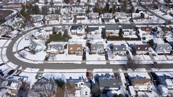 aerial drone camera shot over a suburb of Long Island, NY in the morning, after a snowfall. The houses are arranged neatly around a curved road.