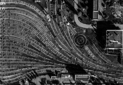 aerial drone creative top view to metro depot heavy rail, subway, tube, metropolitan or underground. Black and white square design composition. Abstract representation of public transport industry