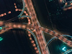 Aerial drone flight over nightroad traffic. Two-level road junction. Top view.