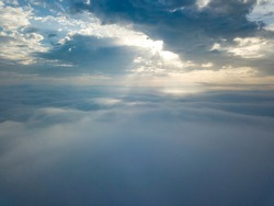 Aerial drone flight over the fog. There are thick clouds of fog below, the sun breaks through the clouds.