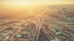 Aerial Drone Flight Photo of highway and overpass with cars and trucks. Road Junction in the big city. Top view. Cityscape in sunset soft light. Instagram vintage filter toning. Kiev, Ukraine, Europe