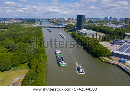 Photo of  aerial drone footage of canal in the province of Utrecht with inland freight ships passing by. The Netherlands. inland vessel. in the back is the A12 highway with the prins clausbrug / galecopperbrug