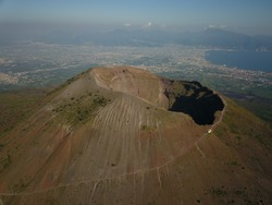 Aerial drone footage of Mount Vesuvius in South Italy on a sunny day.  Its enormity is apparent against the backdrop of Napoli.