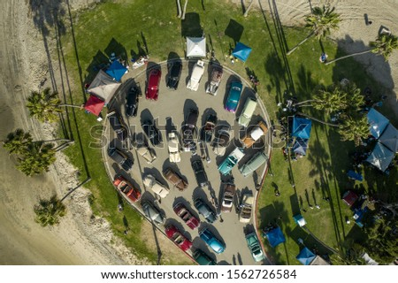 Aerial Drone image of a classic car show in San Diego with Palm Trees and a top down angle on all of the classics