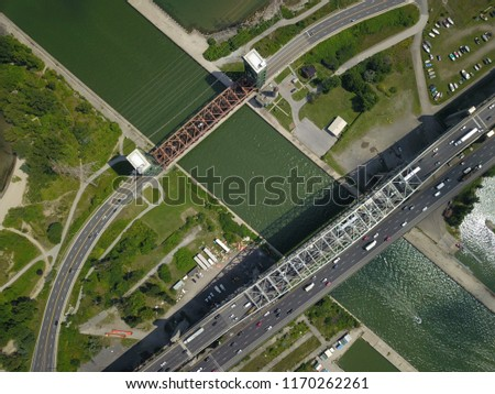 Aerial drone image of a manmade land bridge with a highway, a bridge and a lift bridge at the centre on a bright sunny day. #1170262261