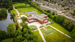 Aerial drone image of a modern and sustainable school with solar panels on the roof reducing CO2 emissions for a better environment.