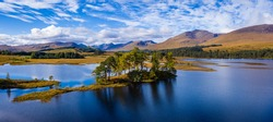 aerial drone image of loch tulla in the argyll region of the highlands of scotland during autumn on a clear bright day showing calm waters on the inland loch