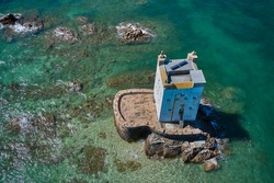 Aerial drone image of Seymour Tower at high tide in the sunshine. Jersey Channel Islands.