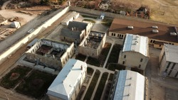 Aerial drone image of The Old Idaho State Penitentiary. Abandoned buildings, some missing roofs, prison walls and walkways.
