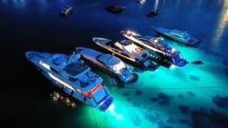 Aerial drone night shot of luxury yachts anchored famous Psarou beach, Mykonos island, Cyclades, Greece