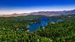 Aerial, drone panorama of Lake Arrowhead in the San Bernardino Mountains, California on a clear, summer day with blue water and sky, purple mountains and green trees
