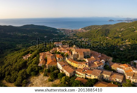 Aerial Drone Panorama of mountain old town Marciana on the islands of Elba Italy with green trees and the mediterranean sea ocean in the background Foto stock ©
