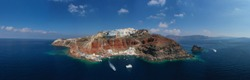 Aerial drone panoramic photo of iconic village of Oia built on a cliff and Ammoudi bay in famous island of Santorini, Cyclades, Greece