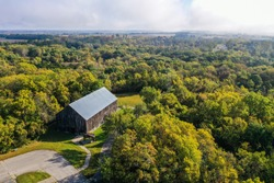 Aerial drone photo of an old, historic, tobacco barn in the public Weston Bend State Park in Missouri north of Kansas City. Trees are just getting their fall colors.
