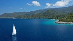 Aerial drone photo of beautiful sail boat with white sails, sailing deep blue Aegean sea