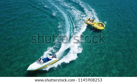 Aerial drone photo of extreme powerboat donut water-sports cruising in high speed in tropical turquoise bay