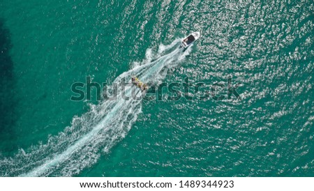 Aerial drone photo of extreme powerboat donut water-sports cruising in high speed in tropical turquoise bay #1489344923