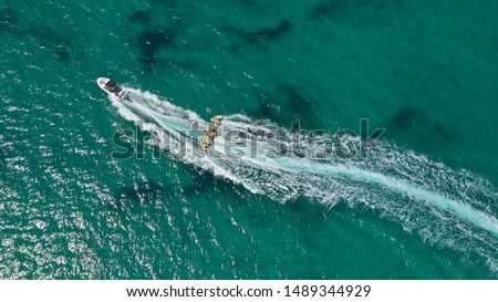 Aerial drone photo of extreme powerboat donut water-sports cruising in high speed in tropical turquoise bay #1489344929