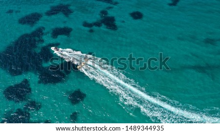Aerial drone photo of extreme powerboat donut water-sports cruising in high speed in tropical turquoise bay #1489344935