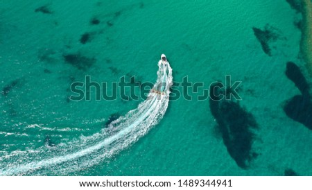 Aerial drone photo of extreme powerboat donut water-sports cruising in high speed in tropical turquoise bay #1489344941