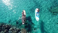 Aerial drone photo of 2 fit men practising SUP or Stand Up Paddle surf board in mediterranean turquoise open sea
